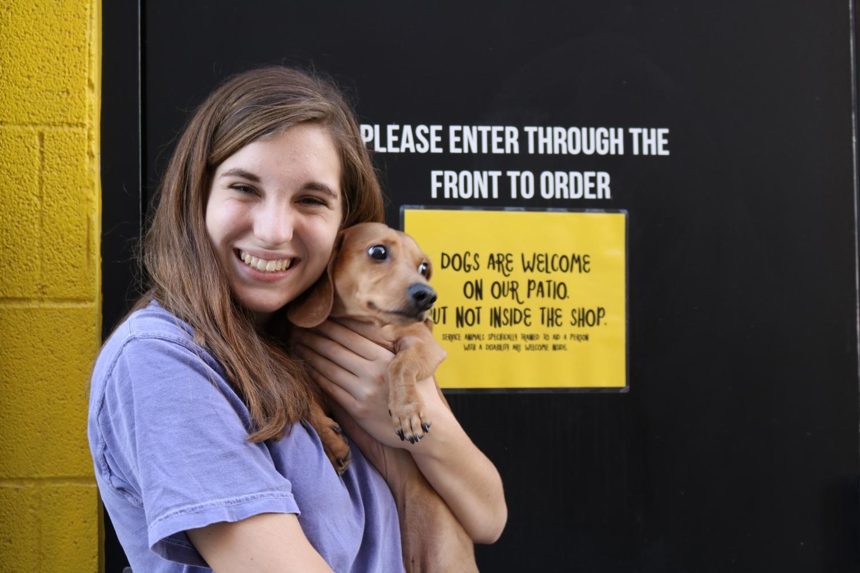 Gracie Jones junior, cuddles with her dog Tex on the porch of Melt Ice Cream.