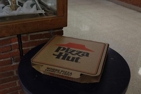 A singular box of Pizza Hut pizza sits upon a trash can, perhaps it is a metaphor that the Hut can finally be out pizza