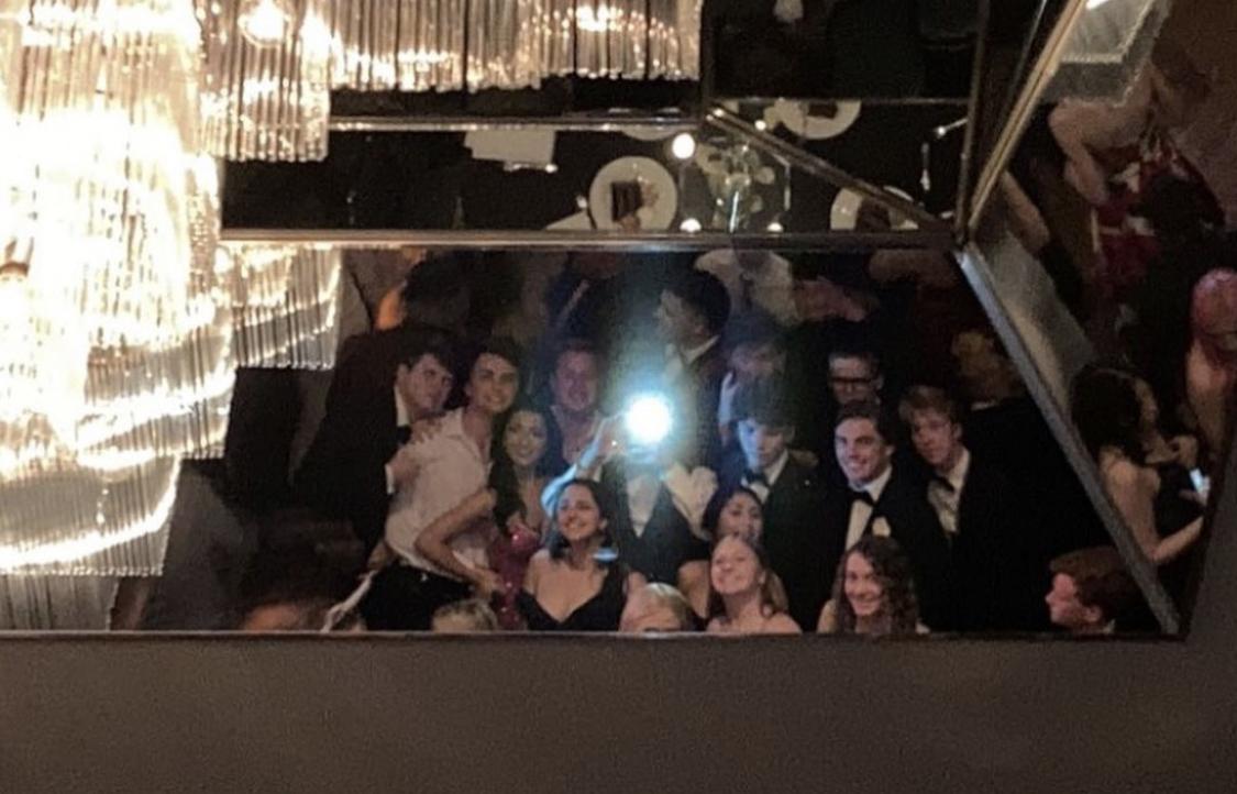 Seniors take mirror selfie on the ceiling over the dance floor.